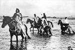 Ute Indians on horseback crossing river